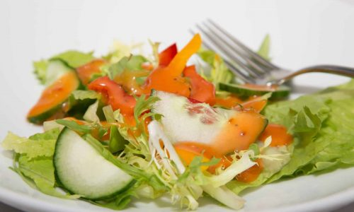 A fresh salad on a white plate with lettuce, red and yellow peppers and cucumbers