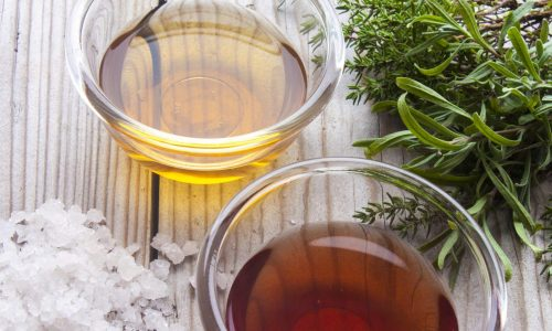 Red wine- and apple vinegar, near rock salt and herbs. On wooden background